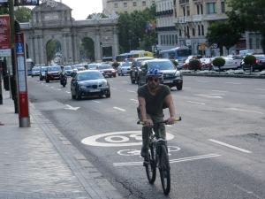 A cyclist on a road wearing a helmet outside of Retiro Park.  Very unusual.